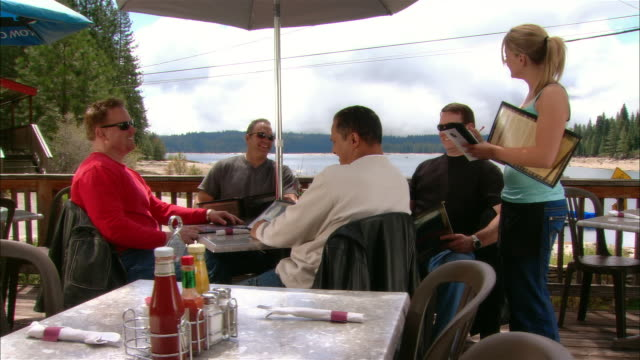 ms waitress taking order of five men sitting at table on restaurant deck/ fresno county, california - serviette stock-videos und b-roll-filmmaterial
