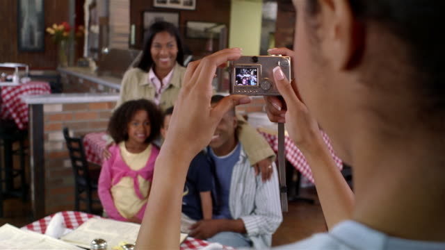 waitress taking picture of family at pizza restaurant with digital camera - digital camera stock videos & royalty-free footage