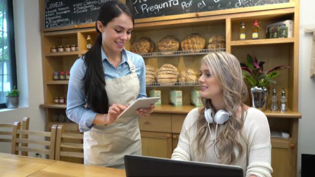 vídeos de stock e filmes b-roll de waitress taking the order from a customer using a tablet - empregada de mesa