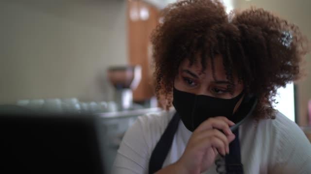 stockvideo's en b-roll-footage met serveerster die op de telefoon spreekt en de orde van de cliënt in een computer registreert - die gezichtsmasker draagt - heropening