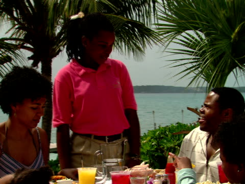 stockvideo's en b-roll-footage met ms,  waitress talking to family of four dining in outdoor restaurant,  harbour island,  bahamas - waaierpalm