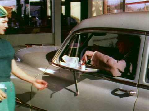 1951 waitress wearing green lifting food tray from car door / man in car nodding to her / industrial