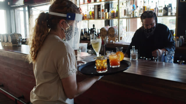 Waitress Wearing PPE During Covid-19 Pandemic Picking Up Drinks from Bar