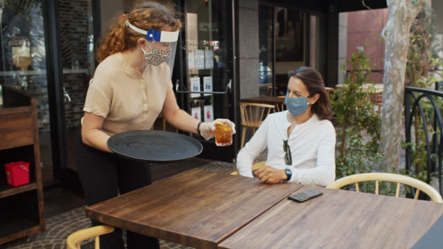 waitress wearing ppe during covid-19 pandemic serves drink to masked customer - hairstyle stock videos & royalty-free footage