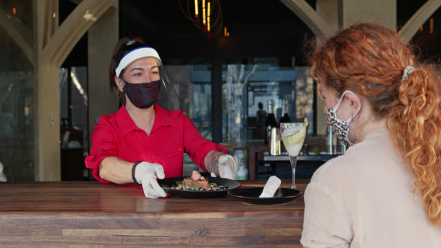 Waitress Wearing PPE During Covid-19 Pandemic Serving Masked Customer Through Window
