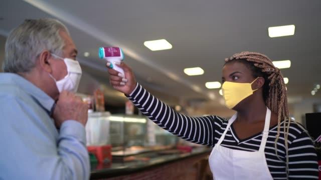 vídeos de stock, filmes e b-roll de garçonete usando máscara facial protetora e medindo a temperatura dos clientes na padaria - medindo