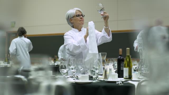 waitress wiping a glass while setting a table in a venue - bicchiere da vino video stock e b–roll