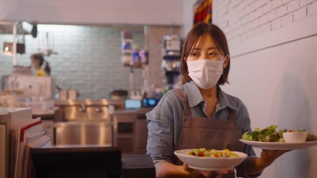 カフェでお客様に食べ物を提供する保護フェイスマスク付きウェイトレス - コーヒーショップ点の映像素材/bロール