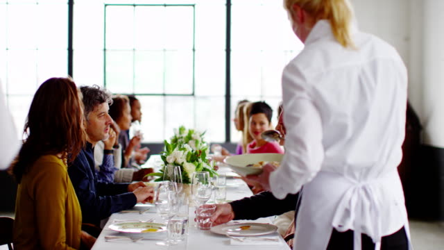 ms waitresses bringing food to table of friends sitting at banquet table  - banquet hall stock videos & royalty-free footage