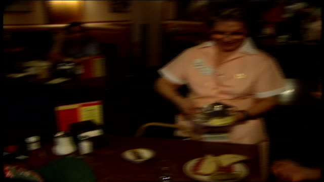 vídeos de stock e filmes b-roll de waitresses in santa hats serving food in a diner at christmas time - chapéu do pai natal