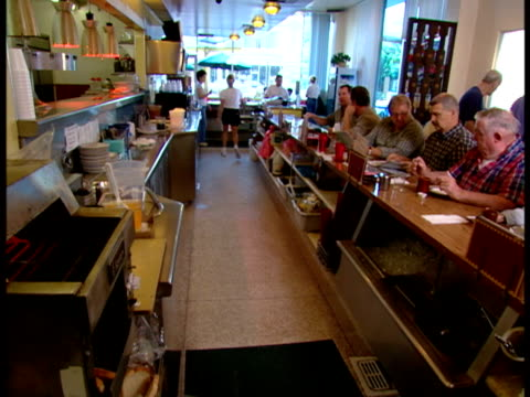 vídeos de stock, filmes e b-roll de waitresses working behind counter, diner full of customers, chefs cooking in kitchen, plates of breakfast foods on kitchen counter, chefs cooking,... - ovo mexido