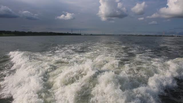 Wake behind luxury yacht sailing in Tokyo Bay