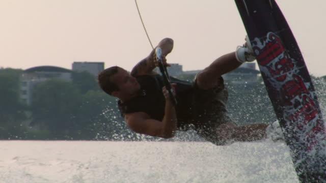 vídeos y material grabado en eventos de stock de slo mo pov ts ms wake boarder doing 360 turn and falling off board into water / potsdam, germany - waterskiing
