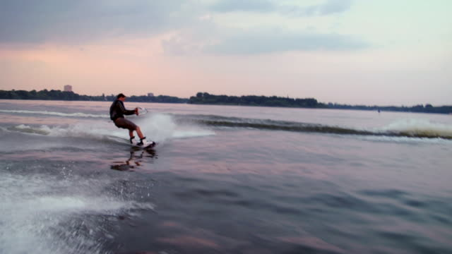 SLO MO TS WS Wake boarder riding wave and doing 360 turn in water / Potsdam, Germany
