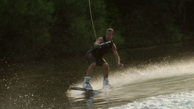 slo mo ws wake boarder riding wave on water / potsdam, germany - wakeboarding stock videos and b-roll footage