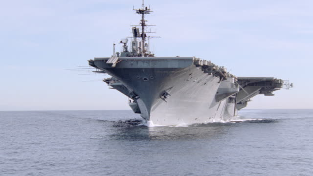 vidéos et rushes de a wake follows an aircraft carrier as it cruises over the ocean. - aller tranquillement