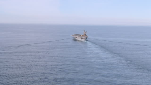 vidéos et rushes de a wake forms in the ocean as an aircraft carrier travels over it. - aller tranquillement