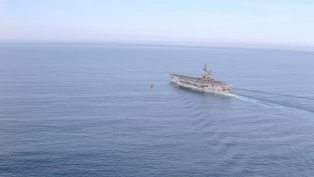 vídeos de stock, filmes e b-roll de a wake forms in the water as an aircraft carrier travels over the ocean. - passear sem destino