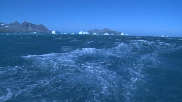 vidéos et rushes de wake from ship with distant icebergs and mountains.  south georgia - île de la géorgie du sud