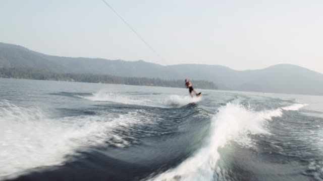 4k uhd: wakeboarder doing huge grab over wake - wakeboarding stock videos and b-roll footage