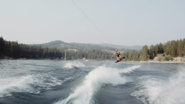 4k uhd: wakeboarder jumping the wake - waterskiing stock videos & royalty-free footage
