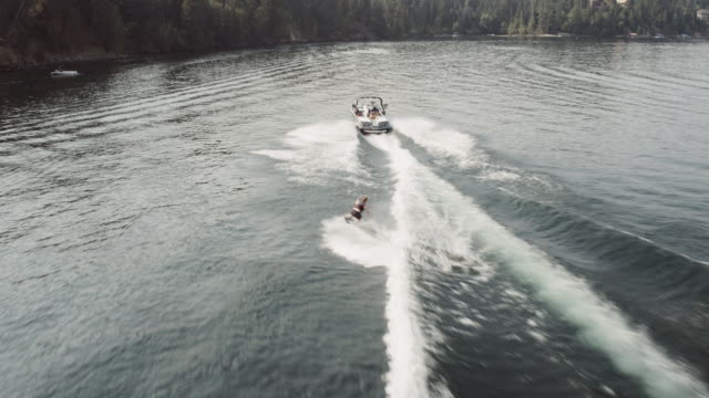 aerial 4k: wakeboarder jumping the wake - wakeboarding stock videos and b-roll footage