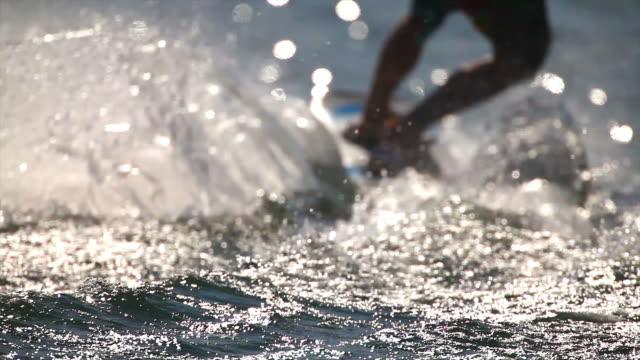 vidéos et rushes de hd wakeboarder sur le lac au rétroéclairage - membres du corps humain