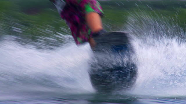 slo mo wakeboarder riding on lake - menschliches bein stock videos and b-roll footage