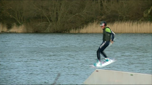 wakeboarders take advantage of flood waters; england: ext jack hammersley along on jump in lake various of jorge gill doing stunts on jumps in lake... - gill stock videos & royalty-free footage