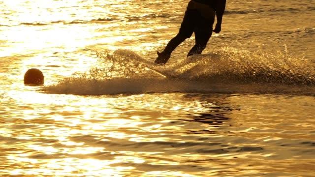 wakeboarding power slide at sunset - waterskiing stock videos & royalty-free footage