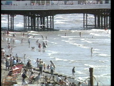 lancashire: blackpool: ext people padding on blackpool beach pull out blackpool pier and promenade mass of tourists along pavement int coach trippers... - week video stock e b–roll