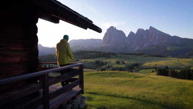 waking up in a high mountain hut and admiring the sunrise over alpine meadow and distant mountains - hut stock videos & royalty-free footage