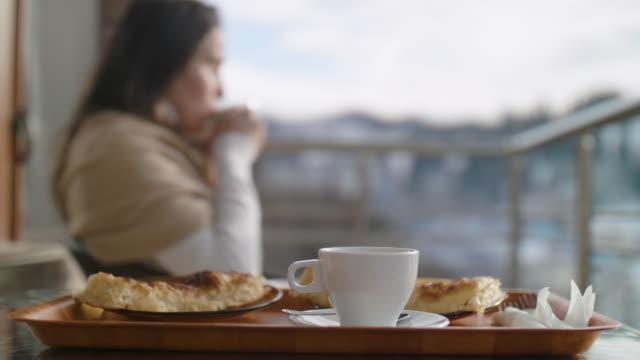 vídeos y material grabado en eventos de stock de despertando en una mañana de invierno en una estación de esquí con una taza de café y desayuno en la habitación durante la pandemia covid-19. contemplación frente a la luz del sol de la mañana. comienzan las vacaciones románticas. - centro de esquí