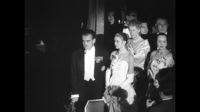 Waldorf Astoria for engagement ball / CU shot Royal Box with crown on top / MS of the prince and Kelly in evening wear standing with other people...