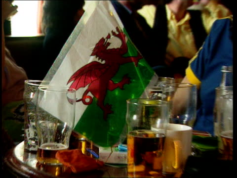 wales antiqueen demo **** for dyfed aberystwyth seq welsh flag on table pull out students sitting around drinking singing - aberystwyth stock videos & royalty-free footage