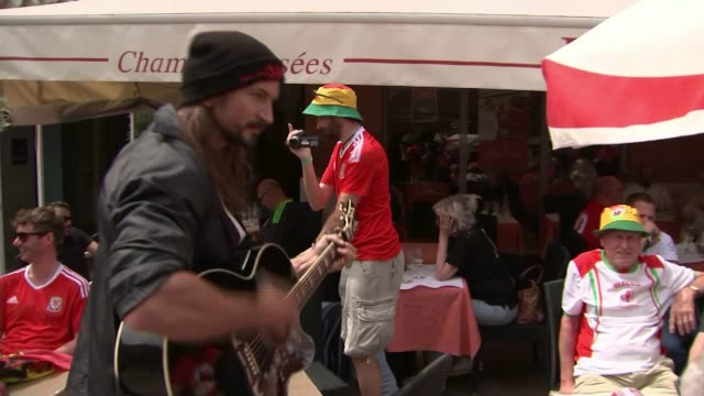 vídeos de stock, filmes e b-roll de wales top group b after win over russia as england are held by slovakia various of man playing guitar as welsh fans sit outside cafe - dedilhando instrumento