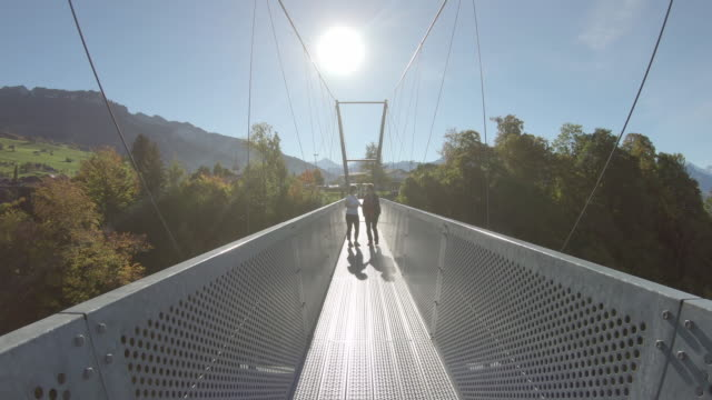 POV walk along metal suspension bridge, towards far side