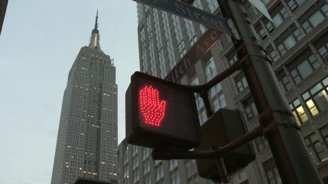 T/L MS LA Walk and don't walk signal with Empire State building in background, day to dusk / New York City, New York, USA