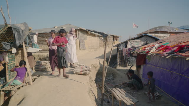 Walk through Kutupalong refugee camp in Bangladesh through homes along a high ridge Bundles of sticks used for building materials line the walkway...
