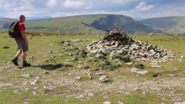 vídeos y material grabado en eventos de stock de walker on the summit cairn of harter fell lake district national park, cumbria, england, uk - montón de piedras