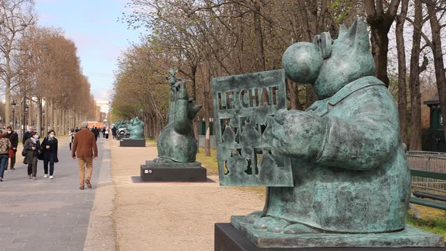 walkers discover the different sculptures during the inauguration of the exhibition the cat « deambule » by philippe geluck on the champs-elysees. on... - カトゥーニスト点の映像素材/bロール
