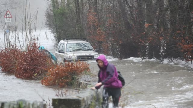 walkers trying to cross raging flood waters on the ambleside coniston road at rothay bridge in the lake district on saturday 5th december 2015 during... - cumbria stock videos & royalty-free footage