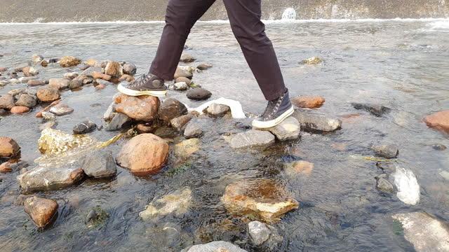 stockvideo's en b-roll-footage met 4k loopt over rivierstenen - de volgende stap