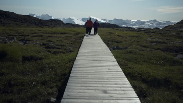 pov: walking along a wooden walkway towards an ice fjord behind a small group of tourists - disko bay, greenland - boardwalk stock videos & royalty-free footage