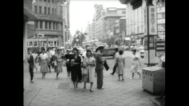 pov walking along pavement with pedestrians in tokyo; 1959 - periodo showa video stock e b–roll