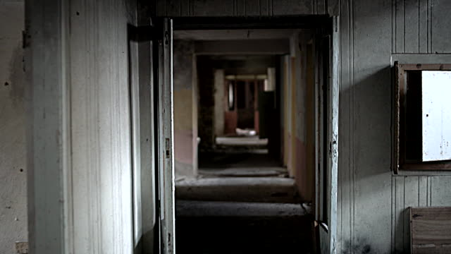 walking along the dark corridor in the abandoned and partially ruined resort near by to ivenets city, belarus, eastern europe - abandoned stock videos & royalty-free footage