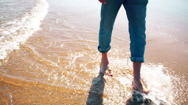 Walking along the sand through shallow sea water.
