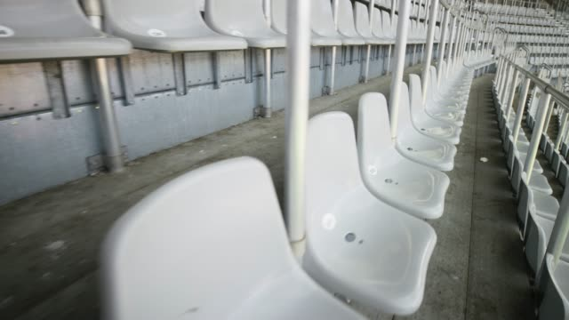 walking amongst the rows of seats on the stadium tribune - ripetizione video stock e b–roll