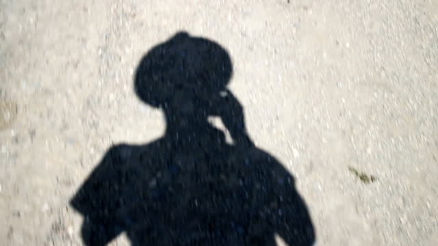 walking and recording his shadow - straw hat stock videos and b-roll footage