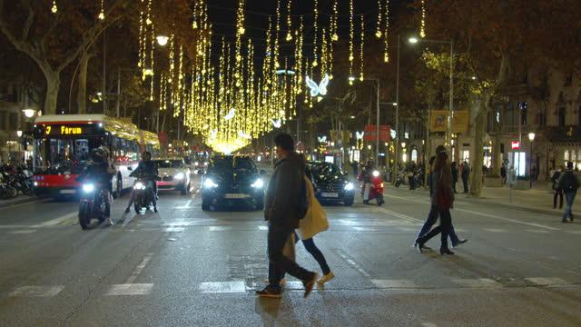 vídeos de stock e filmes b-roll de walking at barcelona with christmas lights. people wearing masks crossing paseo de gracia - centro da cidade
